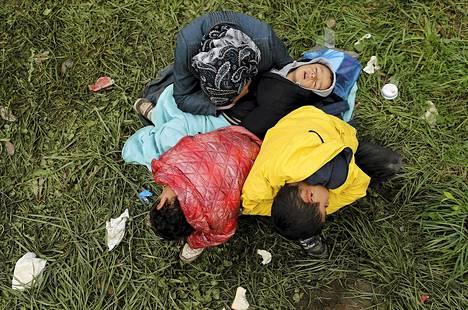 Nainen ja hänen kolme lastaan lepäsivät ruohikolla ylitettyään Kroatian puolelta Sloveniaan lähellä Rigoncea.