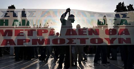 Kreikkalaiset osoittivat mieltään Ateenassa parlamenttitalon edustalla ennen aikaisin maanantaina järjestettyä äänestystä. Kansanedustajat äänestivät laista, joka muun muassa pienentää minimipalkkaa.