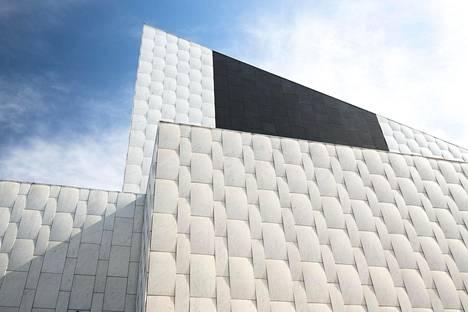 Finlandia-talon pohjoispuolen julkisivu kuvattuna 8. toukokuuta kello 15.23. Auringonsäteet paljastavat marmorilaattojen käyristymät. Varjossa olevassa kohdassa käyristymät eivät näy. Julkisivun musta kivi on Suomen Oulaisista louhittua gabroa.