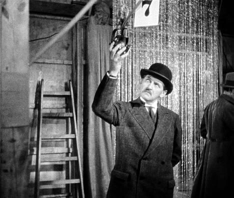 Rikosylikomisario Holzknecht (Ernst Stahl-Nachbaur) on havainnut mikrofonin numero seitsemän.