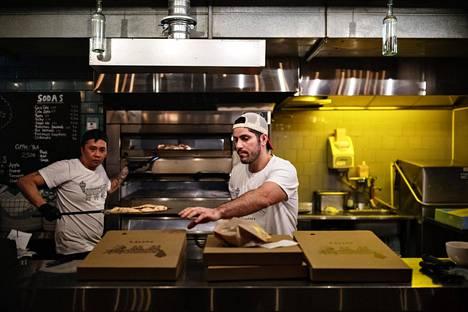 Puttes Bar & Pizzan Alexandrolle (oik) ja Marlonille (vas) riitti töitä pizzan paistossa kotiinkuljetuksia varten. Hiljaisempaa oli kuitenkin kuin normaalina perjantai-iltana.