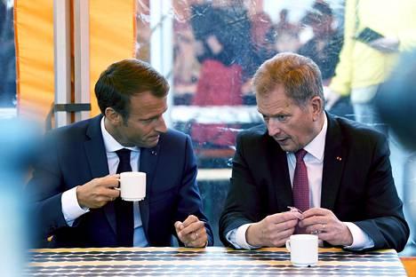 Emmanuel Macron (vas.) ja Sauli Niinistö nauttivat kahvit Kauppatorilla tiedotustilaisuuden jälkeen torstaina.