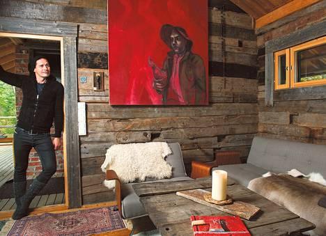 """Saunamökin hirsissä on muun muassa Lapuan vanhaa kirkkoa. Tuvan seinää komistaa Jaakko Karjulan maalaus Mies ja kukko. """"Kun näin taulun, tiesin heti, että se toimisi hirsiseinällä."""""""