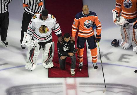 Minnesota Wild's Matt Dumba knelt during the U.S. National Anthem in Edmonton.  To his left stood Darnell Nurse of the Edmonton Oilers and to his left Malcolm Subban of the Chicago Blackhawks.