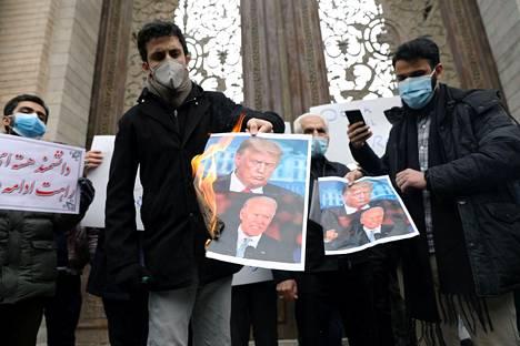 Iranilaiset mielenosoittajat polttivat Joe Bidenia ja Donald Trumpia esittäviä kuvia Teheranissa lauantaina, päivä ydintutkija Mohsen Fakhrizadehin salamurhan jälkeen.