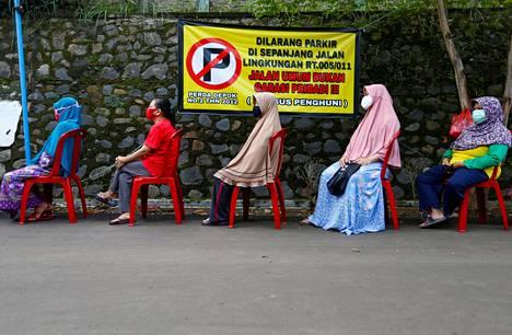 Ihmiset jonottivat vihanneksia Indonesian pääkaupungissa Jakartassa 28. huhtikuuta. Muovituolit oli aseteltu paikallista turvaväliä noudattaen.
