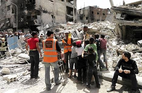 YK:n avustustyöntekijät jakoivat lapsille leipää muiden asukkaiden odottaessa ruoka-avustuksia palestiinalaisten pakolaisleirillä Yarmoukissa Syyriassa 4. toukokuuta.
