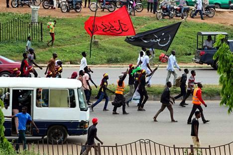 IMN:n (Islamic Movement of Nigeria) mielenosoittajat kantoivat lippuja Nigerian Abujassa 29. lokakuuta. Mielenilmaus päätyi veriseen yhteenottoon armeijan ja poliisin kanssa. Kymmeniä mielenosoittajia kuoli.