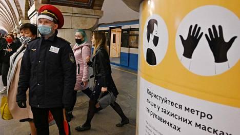 Työntekijä seurasi metromatkustajien liikkeitä Ukrainan pääkaupungissa Kiovassa toukokuun lopussa. Koronarajoitusten vuoksi metrovaunuihin otetaan kerrallaan vain 20 matkustajaa.