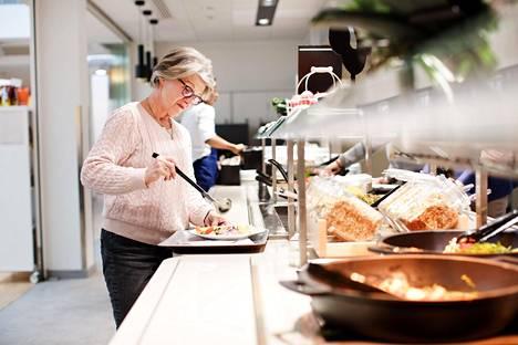 """Sinikka Tuovinen otti lautaselleen lounasta Fazerin ruokalassa Postitalossa. Tuovinen kertoo tarkistavansa aina, että hänen syömänsä liha ja kala on kotimaista. """"En suostu syömään norjalaista lohta"""", Tuovinen sanoo."""