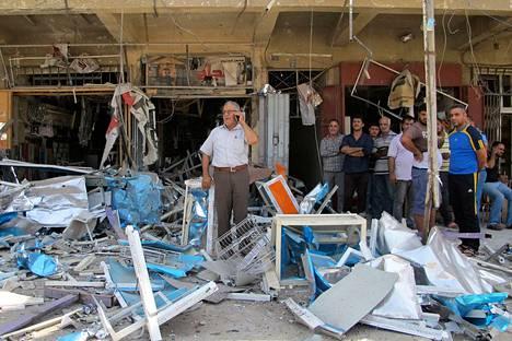 Asukkaat tutkivat pommin jälkiä Bagdadissa lauantaina.