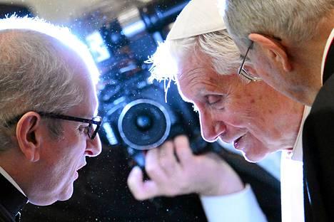 Eroava paavi Benedictus XVI (kesk.) tervehti pappeja tapaamisessa Vatikaanissa torstaina.