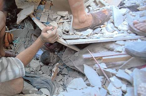 Palestiinalaispoikaa pelastettiin sunnuntaina talon raunioista Rafahissa Israelin tekemän ilmaiskun jälkeen.