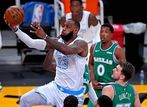 Los Angeles Lakersin LeBron James ohitti Dallas Mavericksin Dorian Finney-Smithin ja Luka Doncicin hyökkäyksessä.