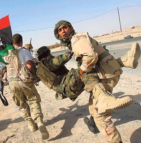Muammar Gaddafia vastaan taistelevat kapinalliset kantoivat haavoittunutta taistelutoveriaan Bani Walidin kaupungin pohjoispuolella syyskuussa 2011.
