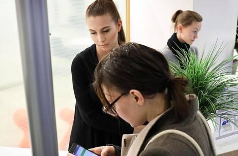 Palveluneuvoja Laura Nyman (vas.) auttaa Julia Lindiä mobiilipankin kanssa tulleessa ongelmassa Nordean konttorissa Helsingin Mannerheimintiellä. Yhä useampi asiakas käyttää pankkipalveluja pääasiassa matkapuhelimella.