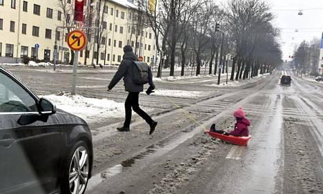 Mies veti lasta pulkalla Helsingissä sunnuntaina 21. helmikuuta.