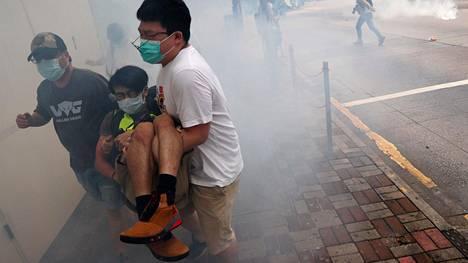 Loukkaantunutta mielenosoittajaa kannettiin pois kyynelkaasupilvestä Hongkongissa sunnuntaina.