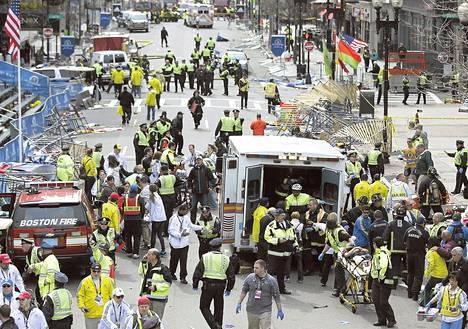 Pelastustyöntekijät antoivat ensiapua räjähdyksissä loukkaantuneille ihmisille Bostonin maratonin maaliviivalla maanantaina. Poliisi vahvisti räjähdykset pommi-iskuiksi.