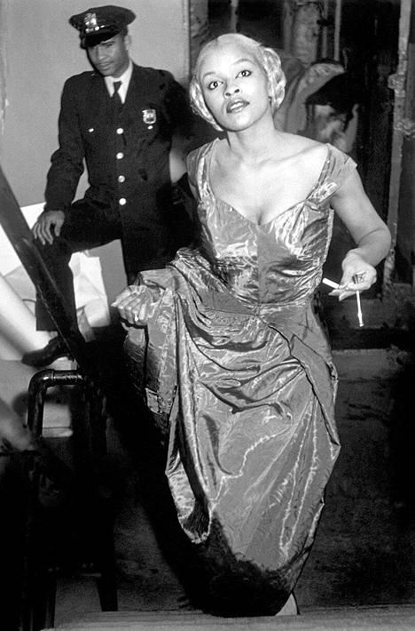 """Malli Charlotte Stribling eli Fabulous odottaa vuonna 1950 takahuoneessa vuoroaan lavalle tilaisuudessa, jossa esiteltiin Harlemin yhteisössä suunniteltuja ja valmistettuja vaatteita. Arnold vietti noin vuoden kiertäen ja kuvaten Harlemia, sen baareja, kirkkoja ja ravintoloita, joissa mustat naiset esittelivät käsitöitään. """"Vaatteet olivat joko mallien itsensä tai paikallisten ompelijoiden tekemiä, osin protestina Seventh Avenuen valkoisten yritysten 'shmatte'-muodille. Se oli yksi kansalaisoikeusliikkeen edelläkävijöistä."""""""