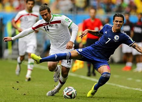 Iranin Andranik Teymourian (vas.) taisteli pallosta Muhamed Besicin kanssa jalkapallon MM-kisoissa.