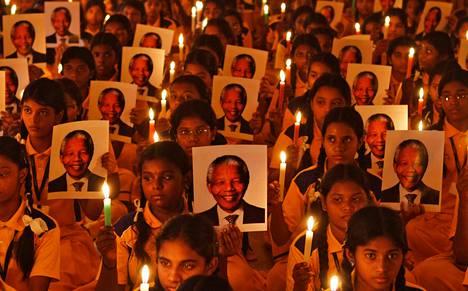 Koululaiset sytyttivät kynttilöitä Nelson Mandelan muistoksi rukoushetken yhteydessä Intian Chennaissa perjantaina.