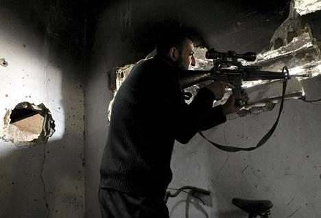 Syyrialaistaistelija asemissaan Homsissa lauantaina.