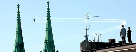 Puolustusvoimien lippujuhlan taitolentokone keräsi katsojia taiteillessaan Johanneksen kirkon tornien takana. Kuva on lukijan ottama.