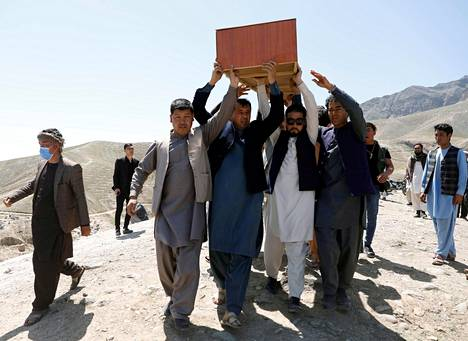 Miehet kantavat lauantaisen pommi-iskun uhrin arkkua Kabulissa, Afganistanissa.