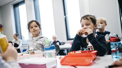 Ayan (vas.) ja Balder nauttivat lounastaan Holmenin peruskoulussa.