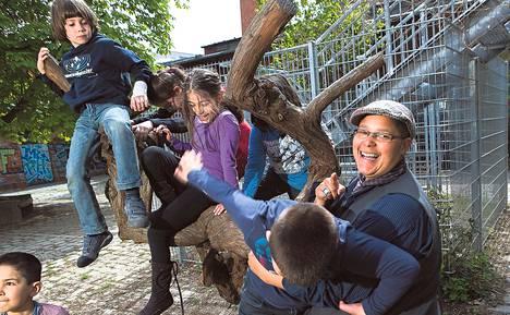 Apuopettaja Sam Lesniewicz (oik.) leikitti lapsia Rosa Parksin koulun pihalla Berliinissä.