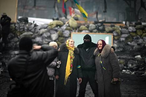 Naiset poseerasivat oppositiota kannattavan mielenosoittajan kanssa tiesulun edessä Kiovassa lauantaina.