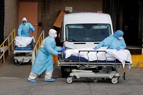 Terveydenhuollon työntekijät kuljettivat koronavirukseen menehtyneitä Wyckoff Heights -terveysasemalla Brooklynissa torstaina.