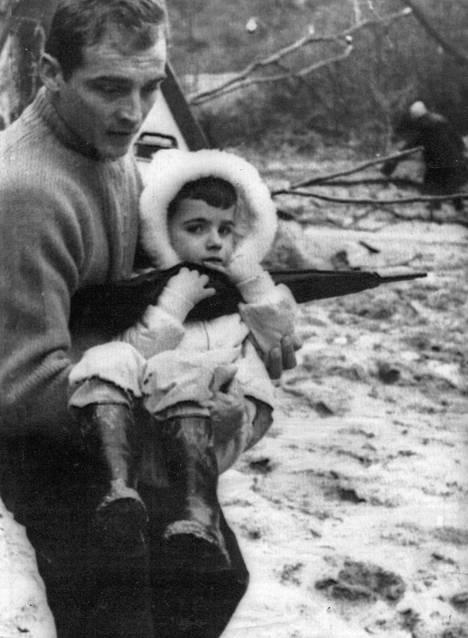Turvaan matkaa vallemossolaispoika isänsä käsivarsilla tulvien runtelemasta kotikylästään.