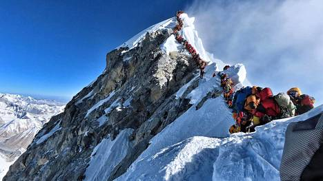 This handout photo taken on May 22, 2019 and released by climber Nirmal Purja's Project Possible expedition shows heavy traffic of mountain climbers lining up to stand at the summit of Mount Everest. - Many teams had to line up for hours on May 22 to reach the summit, risking frostbites and altitude sickness, as a rush of climbers marked one of the busiest days on the world's highest mountain. - LEHTIKUVA / AFP