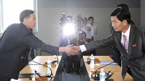 Etelä-Korean neuvottelija Kim Ki-woong (vas.) kättelee Pohjois-Korealisen kollegansa Park Chol-sun kättä maiden välisesissä neuvotteluissa Kaesongin teollisuusalueen uudelleen avaamisesta.
