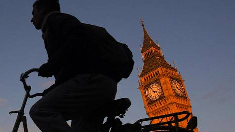 Lontoolaismies pyöräili Britannian parlamenttitalon ja Big Ben -kellotornin ohi.
