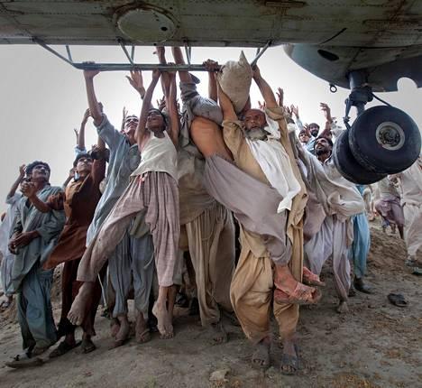 PAKISTAN TULVI. Kesällä 2010 Pakistanin alueella kulkeva Indusjoki tulvi ja aiheutti tuhoa jopa viidesosassa maan alueesta. Tulva vaikutti 20 miljoonan ihmisen elämään ja ravinnonsaantiin, mutta suoraan tulvaveden seurauksena menehtyi vain 2000 ihmistä. Kuvassa punjabilaiset saavat ruoka-apua helikopterista elokuussa 2010.