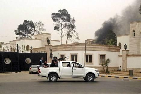 Aseistetut miehet tähtäilivät autosta savun noustessa taustalla Libyan parlamenttitalosta Tripolissa sunnuntaina.
