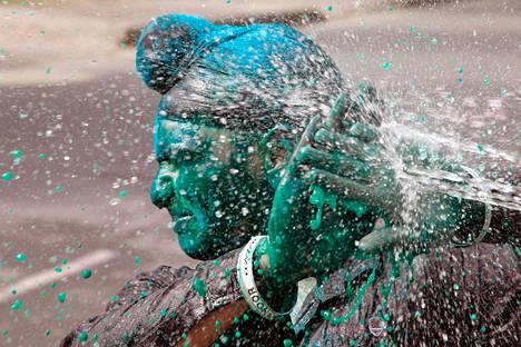 Holi-juhlaa viettävä intialaismies suojaa värjättyjä kasvojaan Chandigarhissa maanantaina.