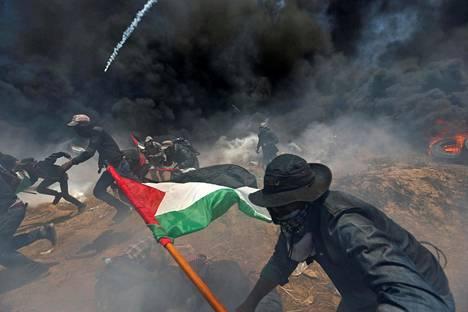 Palestiinalaismielenosoittajat hakivat suojaa Israelin tulitukselta maanantaina.