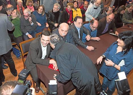 Vasemmistojohtaja Alexis Tsipras (pöydän päässä) sai hurmioituneen vastaanoton kannattajiltaan myöhään maanantai-iltana Ateenassa.