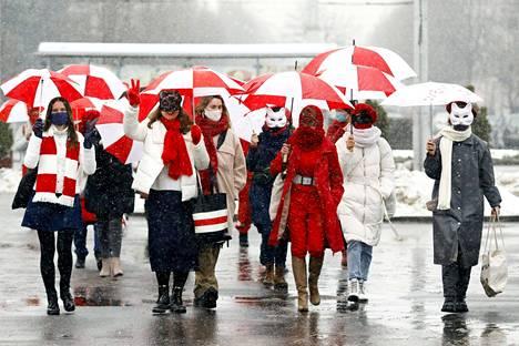 Mielenosoittajien tunnus on Valko-Venäjän aiempi valko-puna-valkoinen lippu. Tammikuun lopulla Minskissä otetussa kuvassa mielenosoittajat ovat sonnustautuneet naamareihin ja kantavat lipun värisiä sateenvarjoja.