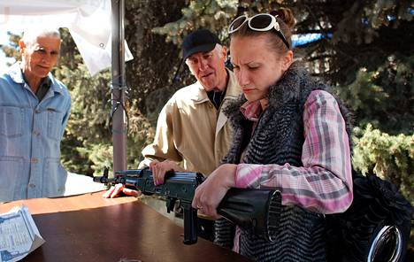 Diana Burova (oik.) ja Sergei Ivanov käsittelivät rynnäkkökivääriä turvallisuuspoliisin rakennuksen edustalla Luhanskissa keskiviikkona.
