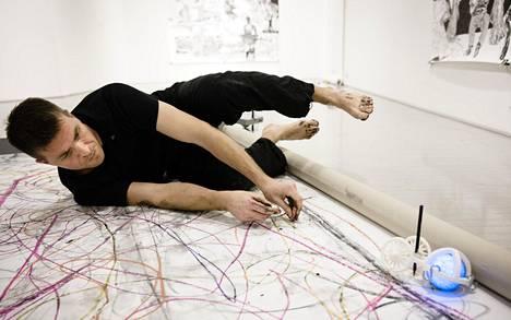 Kuvataiteilija Matti Vainio piirtää usein lattialla. Niin robotinkin kanssa. Sähköisen pallolelun ympärille kynärobotin on rakentanut Vainion kollega Tomi Dufva. Piirtäjärobotti vaihtaa suuntaa törmäyksestä.