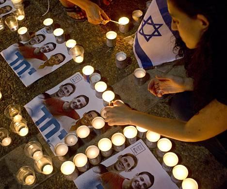 Surevat israelilaiset sytyttivät kynttilöitä kolmen tapetun pojan muistoksi Rabinin aukiolla Tel Avivissa.