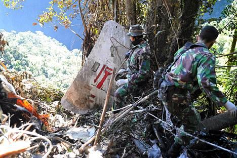 Indonesialaissotilaat tutkivat venäläiskoneen hylkyä puotamispaikalla 12. toukokuuta.