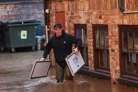 Ilmastonmuutos uhkaa pahentaa Britannian tulvia. Kuvassa mies tulvaveden peittämällä kadulla Yorkin kaupungissa Pohjois-Englannissa tammikuussa.