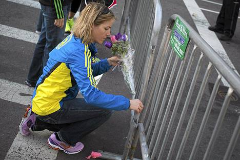 Alison Gardner toi kukkia suljetun maratonalueen aidalle Bostonissa tiistaina.