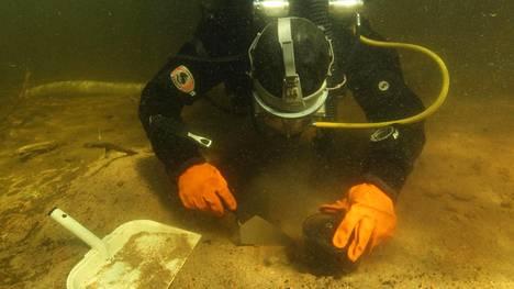Eveliina Salo kaivaa vedenalaista liettä varovasti esiin.
